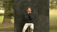 "Guy makes a face & smiles in front of a ""just be you"" sign on chalkboard Stock Footage"