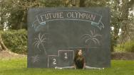 "Stock Video Footage of Girl Drops Into Split In Front Of Chalkboard W/""Future Olympians"" & Podium On It"
