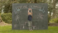 "Cute Girl Sticks Back Flip Landing; Chalkboard with ""Future Olympian"" & Podium - stock footage"