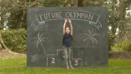 "Stock Video Footage of Cute Girl Sticks Back Flip Landing; Chalkboard with ""Future Olympian"" & Podium"