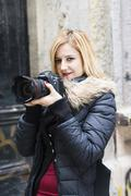Portrait of young woman holding reflex camera - stock photo