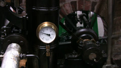 Stationary steam engine pressure gauge and flywheel - stock footage