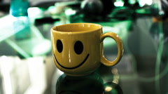 Time lapse of a yellow cup with smile in the office. Happy work-space concept Stock Footage