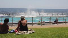 Elderly Couple by a Seaside Pool with Splashing Waves Stock Footage
