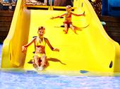 Stock Photo of child on water slide at aquapark.