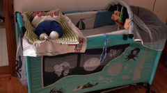 Baby on changing unit of playpen cot Stock Footage