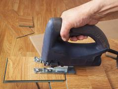 master using an electric jigsaw saws laminated panel - stock photo