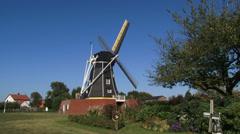 Black tarred beltmolen-type windmill in operation + scale model windmill Stock Footage