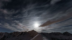 Mountains and moon behind the clouds - stock footage