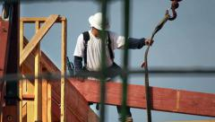 Construction worker unloads cargo at new development site Stock Footage