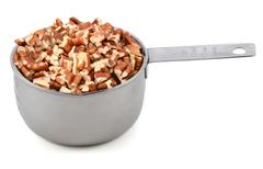 chopped pecan nuts in a metal cup measure - stock photo
