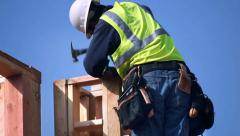 Construction worker installs the wooden column on the new building structure Stock Footage