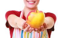 Stock Photo of happy housewife or chef in kitchen apron showing apple isolated