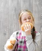 girl bites off a bun - stock photo