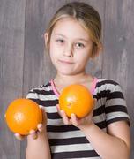 Girl holding  oranges Stock Photos