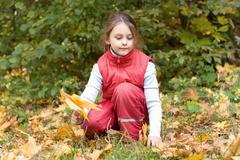 Little girl and autumn leaves Stock Photos