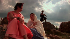 Thracian women talking on a rock behind them playing the flute young Thracian Stock Footage