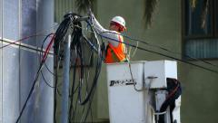 An electrician prepares wiring a power line installation at construction site - stock footage