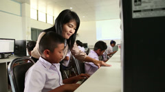 Teacher Helping Asian Student In Computer Lab Stock Footage