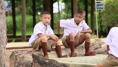 Two Cute Asian Grade School Students Sitting On A Log Stock Footage