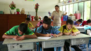 Stock Video Footage of Thai Teacher Checking On Her Students During Test