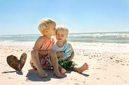 Stock Photo of big brother kissing young child on beach