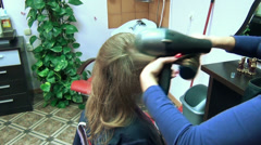 Close view hairdresser dry long client girl hair with blow dryer Stock Footage