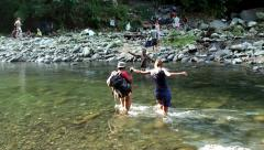 Tourists are wade passing through a mountain river. Stock Footage