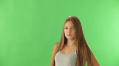 Charming girl expressing disapproval standing on green background and showing Stock Footage