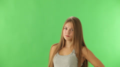 Young woman standing on green background expressing discontent and showing  Stock Footage