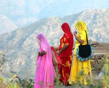 indian women in colorful saris on top of hill - stock photo