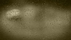 Rain drops on the home window glass with evening traffic background - stock footage