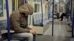 LONDON:  Man with a hoodie sits down in a tube train Stock Footage