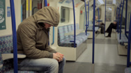 Stock Video Footage of LONDON:  Man with a hoodie sits down in a tube train