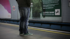 LONDON:  Man with a jacket stands on a platform and waits for a train Stock Footage