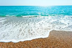 glare of the sun and the sea foamy wave - stock photo