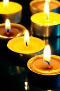 Small yellow burning candle in the dark Stock Photos