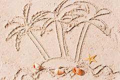 uninhabited island in the ocean and palm trees painted on the sand - stock photo