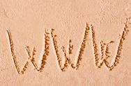 Stock Photo of www written on wet sand at the sea