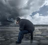 depressed young man sitting on a chair, smoking a cigarette - stock photo