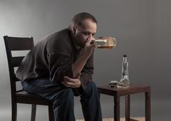 Depressed young man sitting - stock photo