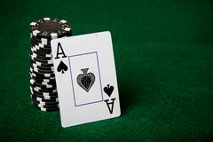 Ace of spades leaning on stack of black poker chips. Stock Photos