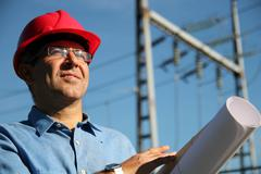 Engineer With Red Hard Hat and Blueprint Under the Power Lines - stock photo