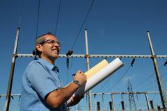Happy Engineer Next to Electrical Substation - stock photo