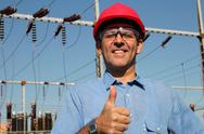 Stock Photo of Successful Engineer in Red Helmet Showing Ok Sign.