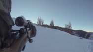 Stock Video Footage of Hunters rifle with the sun, and snow walking behind other hunters.