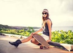 beautiful young woman with a skateboard - stock photo
