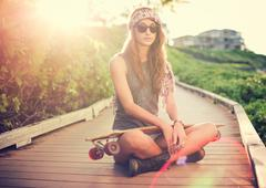 Stock Photo of beautiful young woman with a skateboard