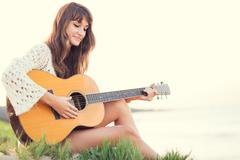 beautiful young woman playing guitar on beach - stock photo