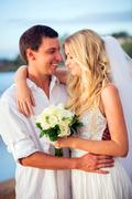 bride and groom at sunset on tropical beach - stock photo